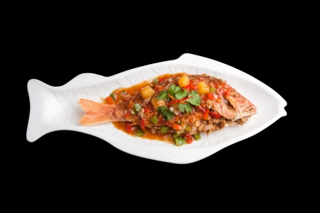 shaped: Freshly prepared Thai style whole fish red snapper dinner with tamarind sauce on a white fish shaped plate isolated over a black background. Stock Photo