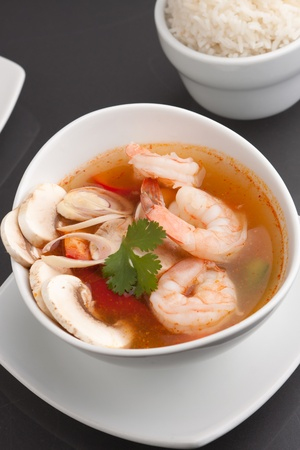 Thai shrimp soup bowl close up with mushrooms and vegetables. photo