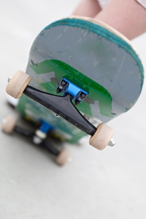 skate board: Close up of a skateboard popped up showing the front trucks and wheels. Shallow depth of field.