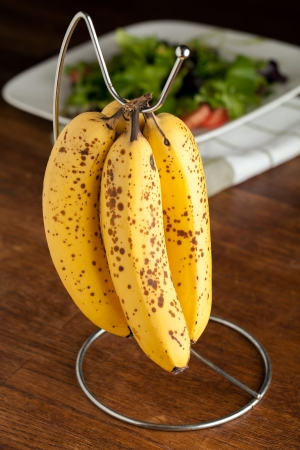 ripened: Spotted bananas that are sweet and ripened hanging on a rack.