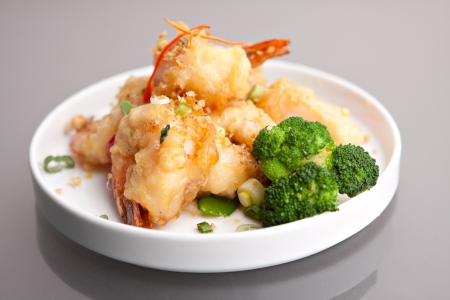 plating: Thai style honey shrimp dish presented beautifully on a round white plate. Stock Photo