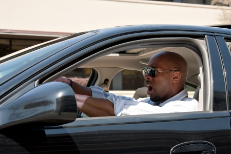 An irritated business man driving a car is expressing his road rage and anger. photo