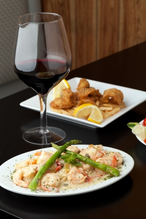 scampi: A delicious shrimp scampi pasta dish with red wine and friend shrimp appetizer in the background.