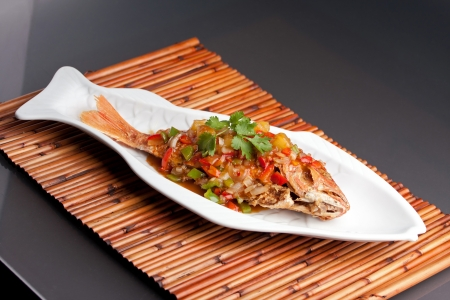 Freshly prepared Thai style whole fish red snapper dinner with tamarind sauce on a white fish shaped plate. photo