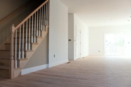 미완성 나무 바닥 계단 및 난간 새로운 주택 건설 객실 인테리어. 전기 및 HVAC 연결은 부분적으로 미완성이다.