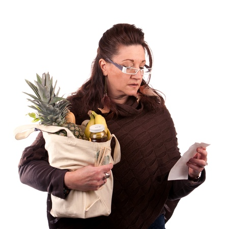 savvy: Middle aged woman carefully examining her register receipt reviewing her grocery shopping bill.
