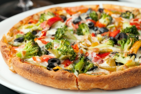 A fresh medium size specialty pizza with extra toppings hot and fresh out of the oven. Shallow depth of field.