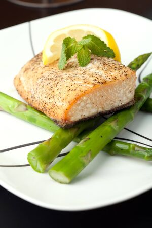grilled fish: Freshly prepared salmon dish on a bed of asparagus spears.