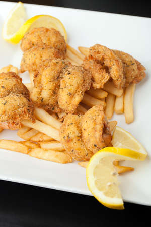 jumbo: Fried shrimp and french fries plate garnished with lemon.