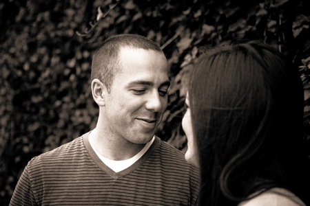Young happy couple enjoying each others company outdoors. Sepia tone.