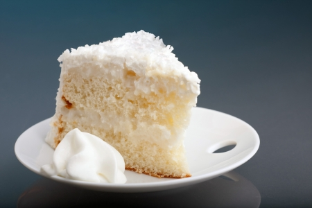 coconut sugar: A fresh piece of coconut cream cake on a white plate with a bit of whipped cream on the side.