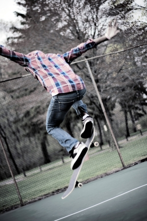 A skateboarder performs tricks in some tennis courts.