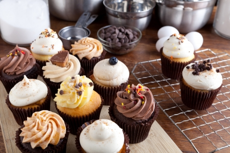 Close up of some decadent gourmet cupcakes frosted with a variety of frosting flavors. Shallow depth of field.