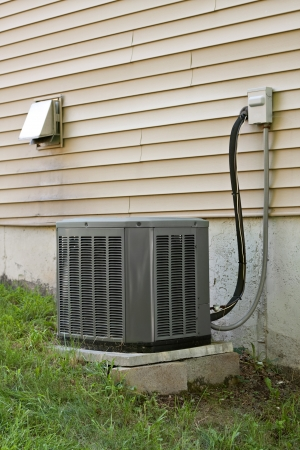 refrigerant: A residential central air conditioning unit sitting outside a home.