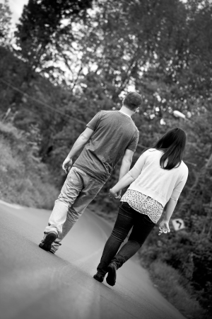 Young happy couple enjoying each others company outdoors walking down an empty road in black and white. photo