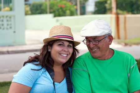 A older Hispanic senior citizen man sits outdoors in a tropical setting with his granddaughter.