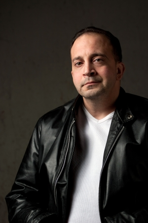 Portrait of a serious middle aged man in his upper 30s wearing a leather jacket in front of a grungy background. photo