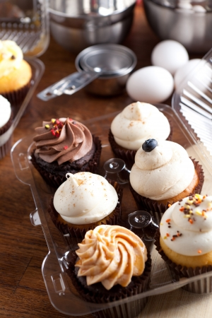 Close up of some decadent gourmet cupcakes frosted with a variety of frosting flavors