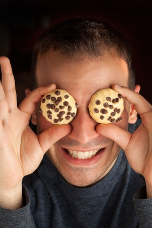 silliness: Crazy man holds cookies over his eyes. Stock Photo