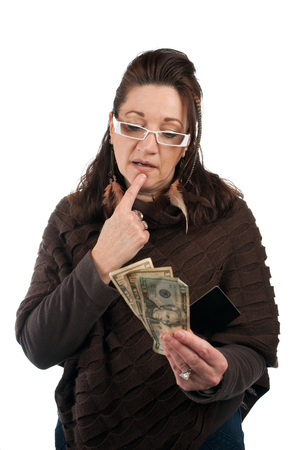 lucrative: Middle aged woman carefully trying to decide between using old fashioned cash or a plastic credit or gift card.