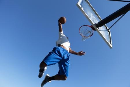 Een jonge basketballer rijden op de Hoop met enige fantasie beweegt.