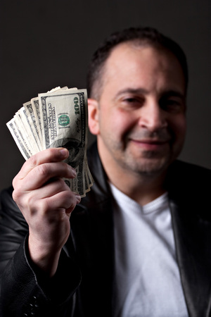 A happy man holds a handful of green American money with selective color. photo