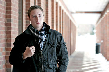 A portrait of a young man standing in an outdoor corridor with his backpack. photo