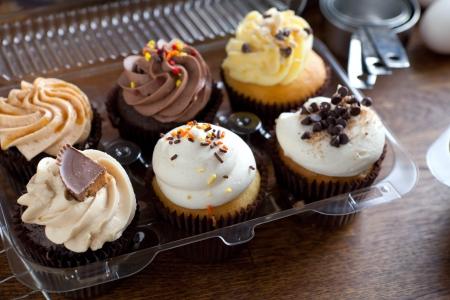 Close-up van een aantal decadente gastronomische cupcakes frosted met een verscheidenheid van glazuur smaken. Ondiepe scherptediepte.