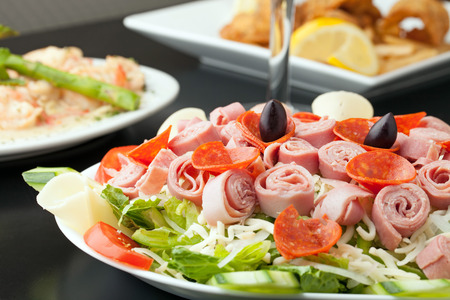 kalamata: A delicious looking tossed chefs salad or antipasto with meat cheese and kalamata olives.