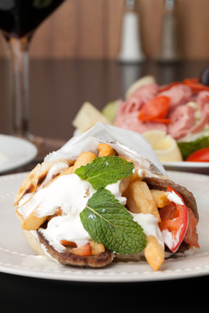 field mint: Traditional Gyro sandwich with meat  tzatziki sauce tomato onions and fried potato garnished with mint. Shallow depth of field. Stock Photo