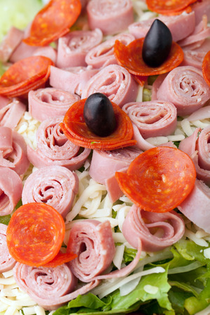 A delicious looking tossed chefs salad or antipasto with meat cheese and kalamata olives. photo