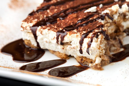 Slice of delicious tirimisu cake on a white plate garnished with cocoa power and drizzled chocolate sauce.