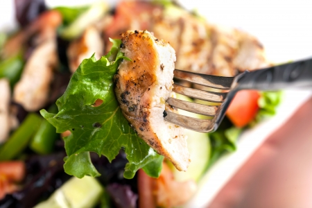 Freshly prepared grilled chicken chef style salad with tomato cucumber green pepper and romaine lettuce. photo