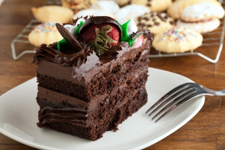chocolate covered strawberries: Italian cookies and a decadent slice of chocolate cake with iced flowers and chocolate covered strawberries on a plate with a fork. Stock Photo