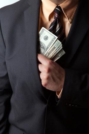 Close-up van een bedrijf mans hand verbergen geld in zijn pak jaszak.