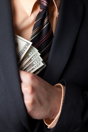 theft: Close up of a business mans hand hiding money in his suit jacket pocket.