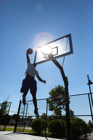 A young basketball player going up for a dunk.  Intentionally back lit with bright lens flare coming through the clear backboard. photo
