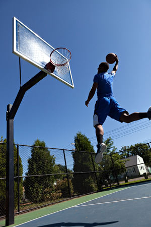 dunk: A young athlete flying through the air to dunk the ball into the basket.