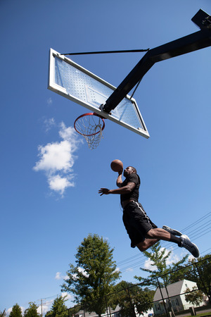 A young basketball player driving to the hoop with some fancy moves. photo
