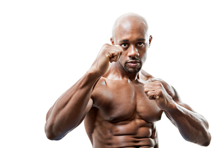 martial artist: Ripped and muscular martial artist holding his fists up isolated over a white background. Great boxing or fitness concept. Shallow depth of field.