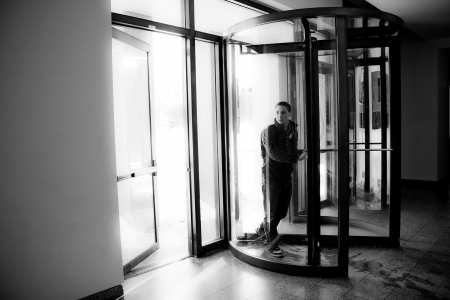 exiting: Young man in his twenties walks through a revolving doorway entrance. Black and white. Stock Photo
