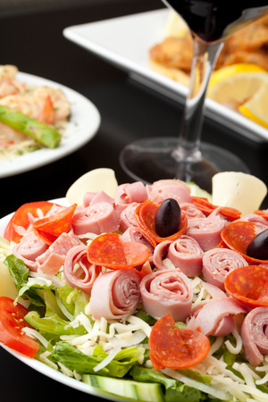 italian foods: A delicious looking tossed chefs salad or antipasto with meat cheese and kalamata olives.