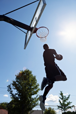 Back lit silhouette of a basketball player going up for a reverse jam. photo