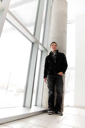 A young man standing by some large windows from a low angle perspective. photo