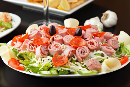 cold cuts: A delicious looking tossed chefs salad or antipasto with meat cheese and kalamata olives.