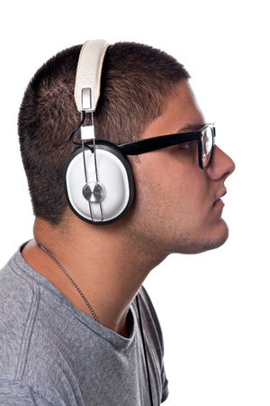 A young man listens to music with a set of head phones over a white background. photo