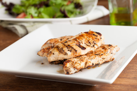 Freshly prepared grilled chicken breasts and salad ingredients. photo