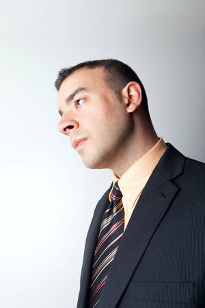 Young business man that looks worried or contemplative isolated over a silver background. photo