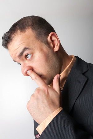 embarassment: Business man sneaking his finger up his nose.