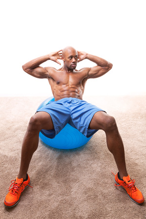 jacked: Muscular man doing ab crunches on an exercise ball.   Stock Photo